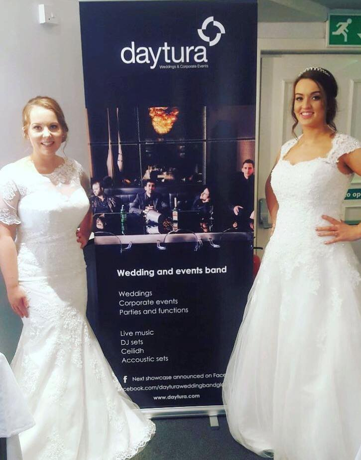 two girls in bridal wear pose infront of daytura banner