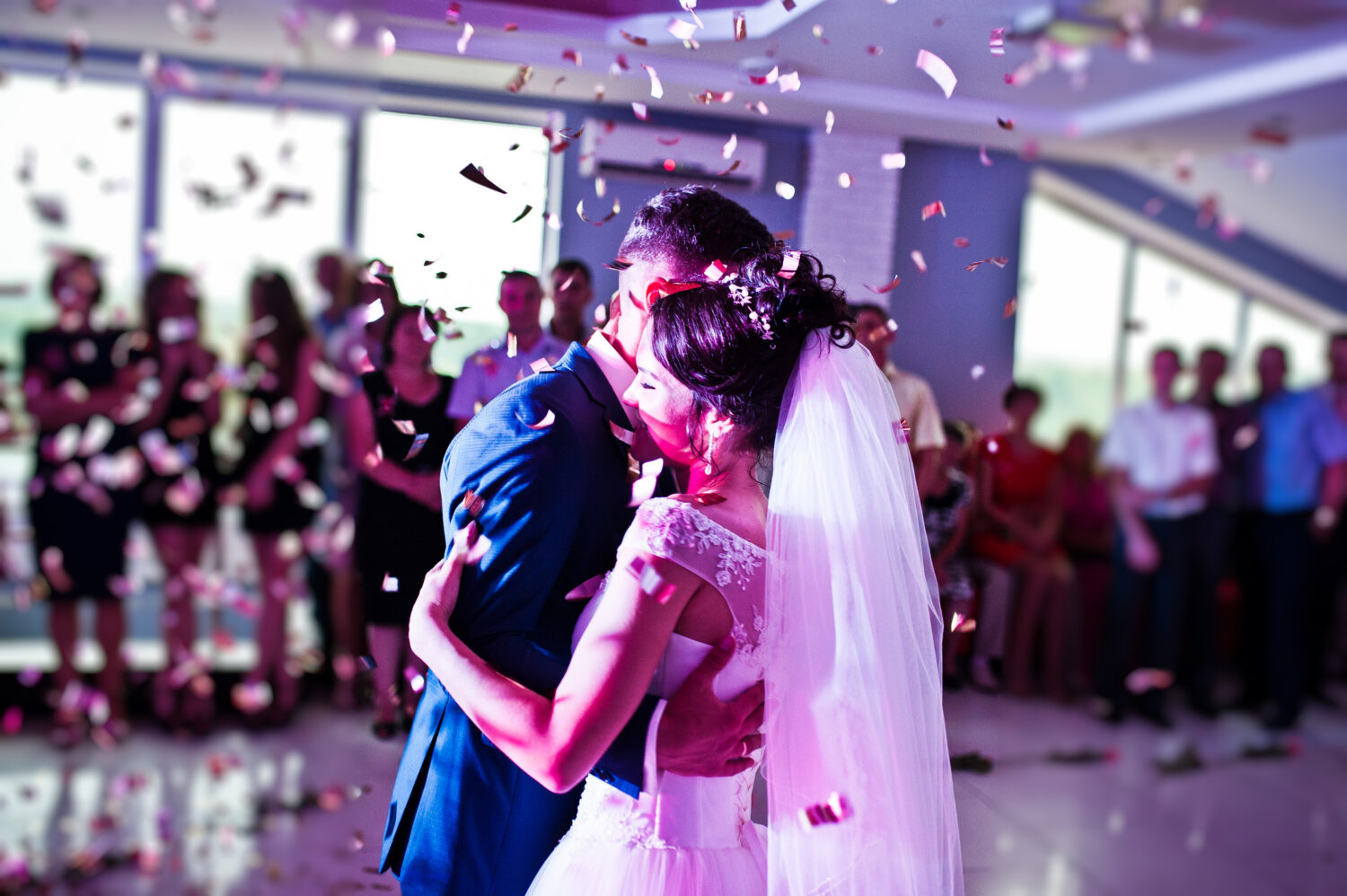 husband and wife embrace as confetti falls