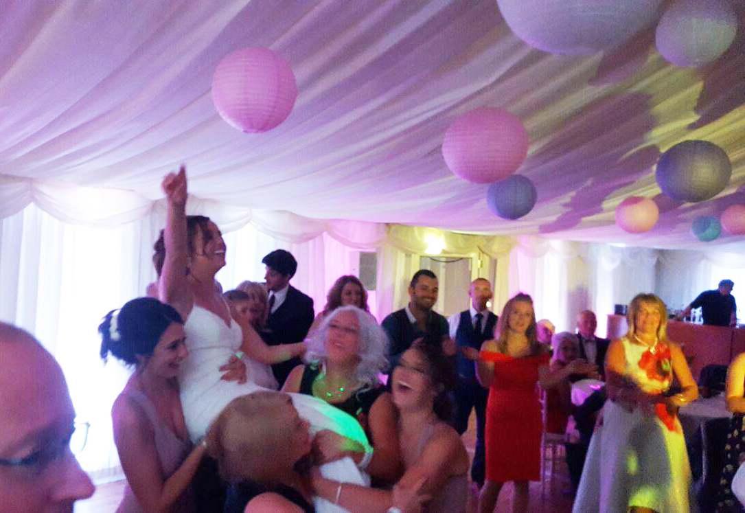 new bride held up in the air by guests