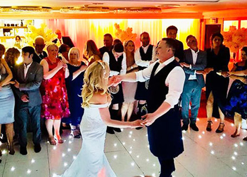 newly weds hold hands on dancefloor at their wedding